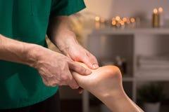 Mãos masculinas que fazem a massagem do pé Fotos de Stock Royalty Free