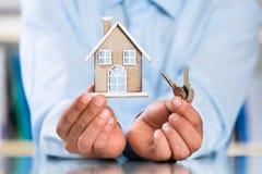 Mãos masculinas que guardam a casa diminuta e a chave da casa Fotografia de Stock