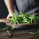 Mãos masculinas que guardam o alimento saudável de madeira cru do vegetariano da placa de corte do feijão verde imagem de stock