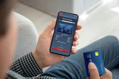 Mãos masculinas que guardam o cartão em linha da compra e de crédito do app do telefone imagem de stock royalty free