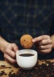 Mãos masculinas que guardam o copo da cookie e de café foto de stock