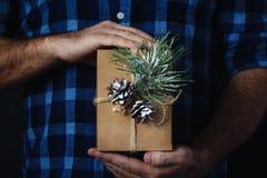 Mãos masculinas que guardam o fundo escuro do Natal do fundo do presente caseiro do Natal foto de stock