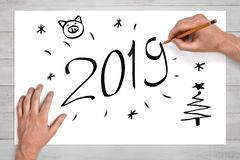 Mãos masculinas que guardam o lápis acima da folha de papel branca com 'os 2019 'sinais, caras do porco, árvores de Natal e floco fotografia de stock royalty free
