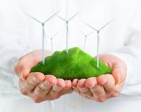 Mãos masculinas que guardaram um monte verde com turbinas eólicas Fotografia de Stock