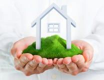 Mãos masculinas que guardaram um monte verde com uma casa pequena Foto de Stock