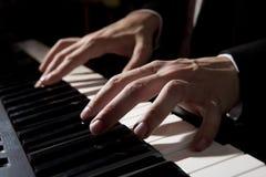Mãos masculinas que jogam o piano Fotografia de Stock