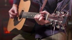 Mãos masculinas que jogam uma música em uma guitarra acústica