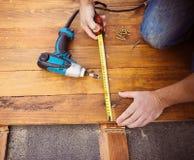 Mãos masculinas que medem o assoalho de madeira Imagem de Stock Royalty Free