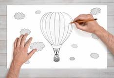 Mãos masculinas que tiram um balão de ar quente entre as nuvens com um lápis em um Livro Branco na vista próxima fotografia de stock royalty free