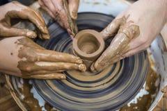 Mãos masculinas que trabalham com a protuberância da argila na roda de oleiro imagens de stock