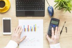 Mãos masculinas que trabalham na calculadora e no portátil Desktop do escritório no fundo de madeira Equilíbrio de contas imagens de stock royalty free