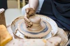 Mãos masculinas sujas que trabalham com a protuberância da argila na roda de oleiro imagens de stock royalty free