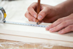 Mãos masculinas usando a fita de medição na placa de madeira Imagens de Stock Royalty Free