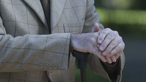 Mãos masculinas velhas que inclinam a vara de passeio, apoio social dos pensionista, inabilidade vídeos de arquivo