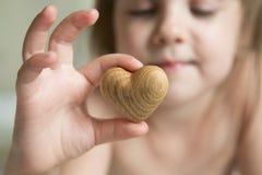 Mãos minúsculas do bebê para guardar o coração de madeira Imagens de Stock Royalty Free