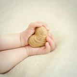 Mãos minúsculas do bebê para guardar o coração de madeira Fotos de Stock Royalty Free