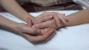 Mãos mornas das filhas que afagam e que acalmam para baixo a mãe doente na cama, auxílio video estoque