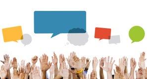Mãos multi-étnicos levantadas com bolhas do discurso Fotografia de Stock Royalty Free