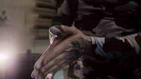 Mãos musculares Tattooed de um fim de aplauso do talco do homem acima no movimento lento filme