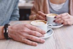Mãos na tabela que guarda xícaras de café Fotografia de Stock Royalty Free