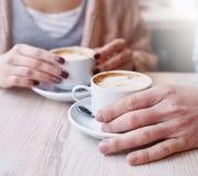 Mãos na tabela que guarda xícaras de café Fotografia de Stock