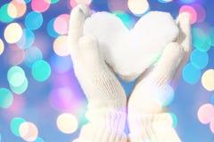 Mãos nas luvas brancas que guardaram o coração da neve Imagens de Stock