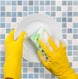 Mãos nas luvas que lavam o prato na cozinha imagens de stock