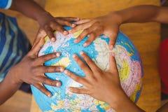 Mãos no globo na sala de aula Imagens de Stock Royalty Free