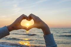 Mãos no sol de quadro da forma do coração fotos de stock royalty free