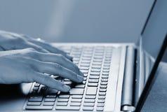 Mãos no teclado Trabalhador de escritório que datilografa no teclado no portátil foto de stock