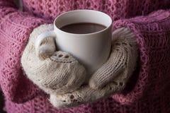 Mãos nos mitenes feitos malha que guardam um copo do coffe Fotografia de Stock