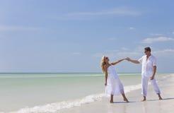 Mãos novas felizes da terra arrendada da dança dos pares na praia Imagens de Stock