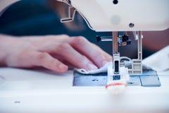 Mãos ocupadas na máquina de costura. Foto de Stock