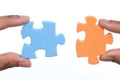 Mãos para unir duas partes do enigma de serra de vaivém Imagem de Stock