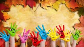 Mãos pintadas coloridas na frente de muitas folhas coloridas Fotos de Stock Royalty Free