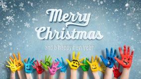 Mãos pintadas das crianças com smiley na frente do fundo do Natal Imagens de Stock Royalty Free