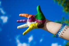 Mãos pintadas das crianças no backgrobnd do céu azul Fotos de Stock