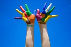 Mãos pintadas das crianças no backgrobnd do céu azul Imagens de Stock Royalty Free