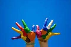 Mãos pintadas das crianças no backgrobnd do céu azul Fotografia de Stock Royalty Free
