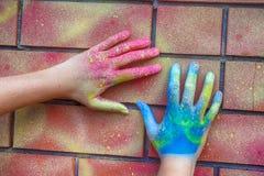 Mãos pintadas na parede de tijolo Imagem de Stock