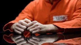Mãos prendidas close up da pessoa, prisioneiro que fala ao advogado durante a interrogação fotos de stock