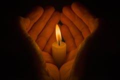 Mãos protetoras em torno de uma vela ardente Imagem de Stock