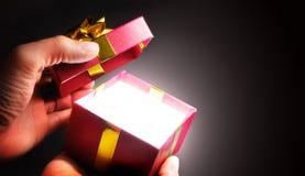 Mãos que abrem uma caixa de presente vermelha com a fita na sombra Fotografia de Stock Royalty Free