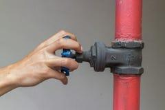 Mãos que abrem a válvula industrial da mão Fotografia de Stock Royalty Free