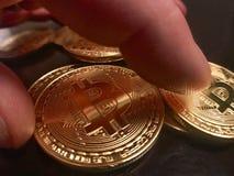 Mãos que agarram um bitcoin dourado Imagens de Stock Royalty Free