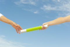 Mãos que alcangam o bastão para trabalhos de equipa Fotografia de Stock