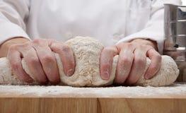 Mãos que amassam a massa de pão de pão Imagens de Stock