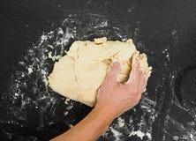 Mãos que amassam a massa pegajosa Imagem de Stock