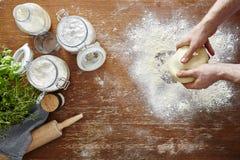 Mãos que amassam a tabela de madeira e a farinha da massa caseiro na cozinha Foto de Stock