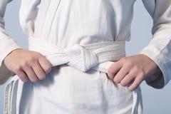 Mãos que apertam a correia branca em um adolescente vestida no quimono Imagens de Stock Royalty Free
